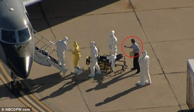 A man in plain clothes was seen on the tarmac Wednesday afternoon, as the second Ebola patient (in yellow hazmat suit) boarded a flight to Atlanta, Georgia
